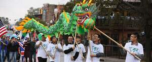 International students holding dragon in homecoming parade.